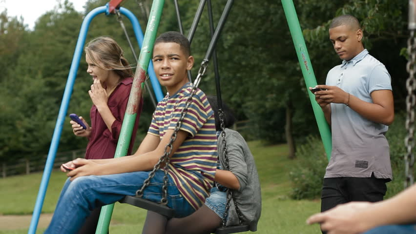 Teens On Cell Phones - Teenagers Hanging Out By Some Swings And Using Mobile  Phones Stock Footage Video 3843023 | Shutterstock