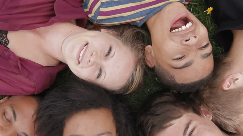 Teens lying on grass - A diverse group of teenagers lying on the grass looking up towards the camera | Shutterstock HD Video #3843161