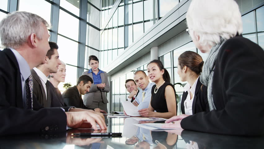 A confident and happy business team of mixed ages and ethnicity are holding a meeting in a light, modern office building. They applaud a comment from one of the group members. | Shutterstock HD Video #3847946