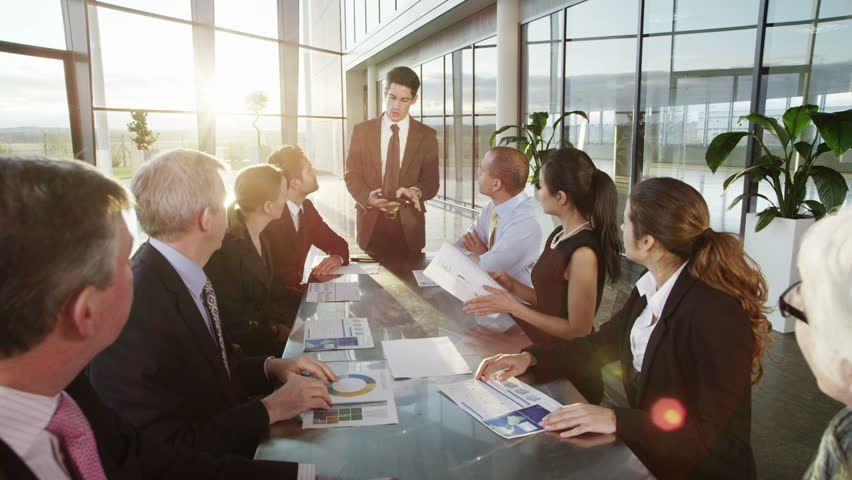 A confident and attractive business team of mixed ages and ethnicity are holding a meeting in a light, modern office building. They are discussing ideas for their business development.  | Shutterstock HD Video #3849596