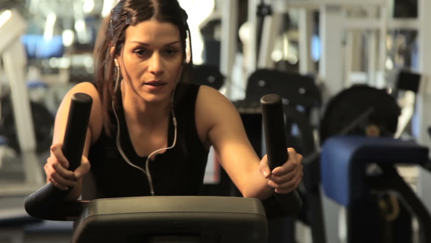 Exercise bike - A woman exercising on a stationary bike in a gym