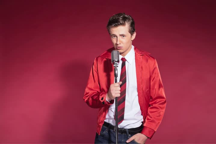 Retro 50s style male singer with vintage microphone wearing red jacket with tie. Studio shot against red background. Stop motion. Time lapse. No audio.