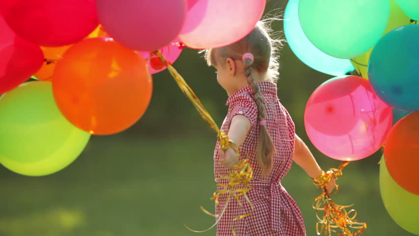 Child spinning with balloons in the park.  Girl looking at camera