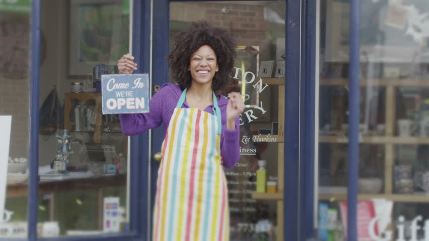 A happy and excited female shopkeeper stands outside