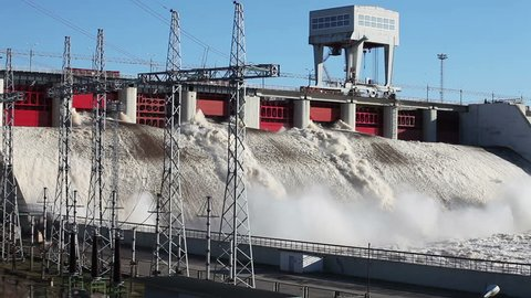 Spring flood water flowing on hydroelectric power station dam