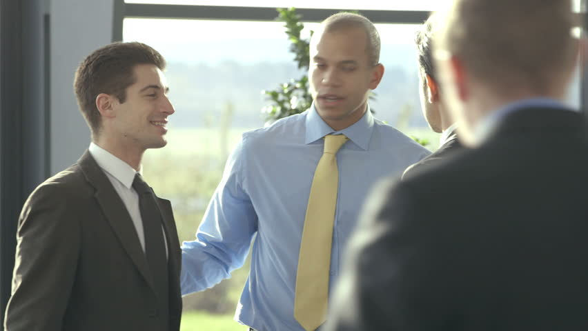 Confident and attractive business team of mixed ethnicity meet and shake hands in the lobby of a busy modern office building.  | Shutterstock HD Video #3871574