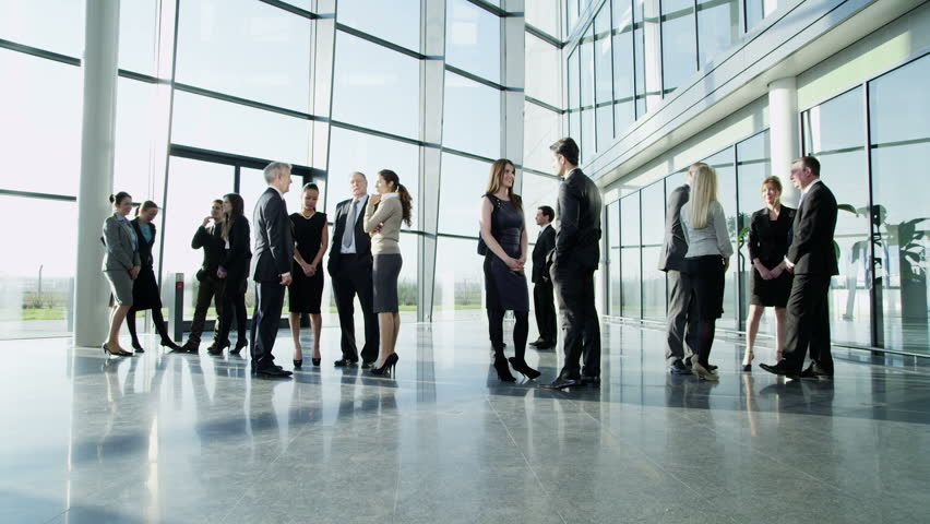 Diverse group of business people, stand and chat to each other in a light and modern glass fronted office building on a bright day. In slow motion.   Shutterstock HD Video #3872432