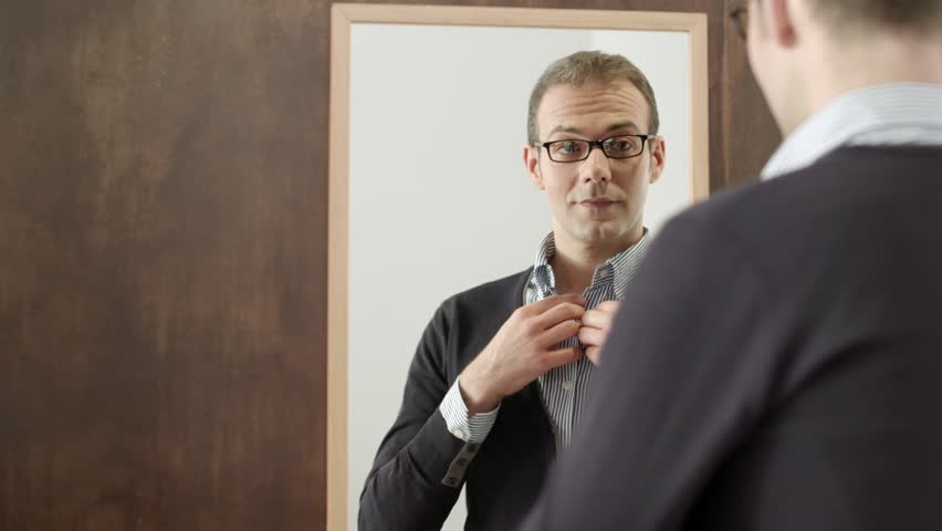 People and clothes, portrait of happy young man with glasses getting ready, dressing up, smiling, looking at mirror in fashion store