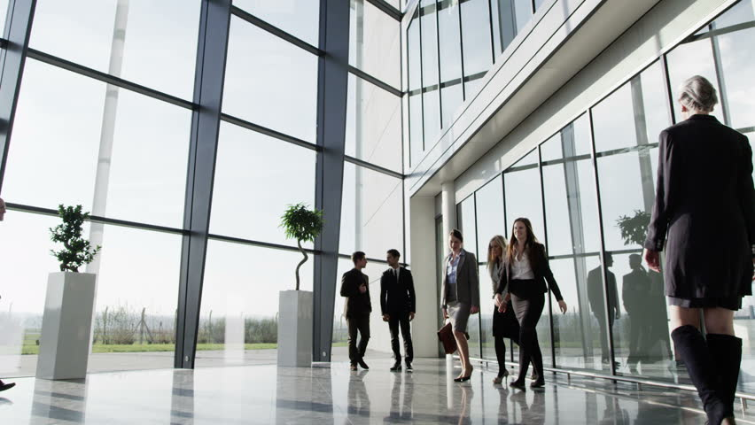 Three businessmen meet and shake hands in a busy modern office building on a bright day. In slow motion. | Shutterstock HD Video #3893453