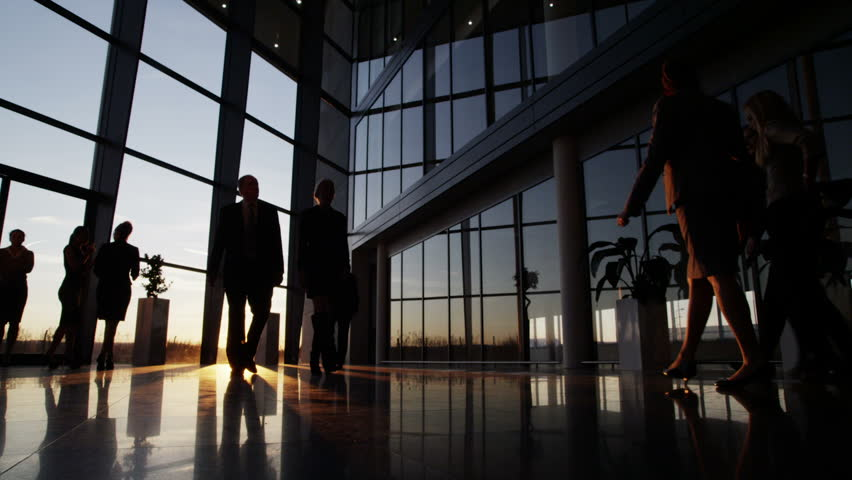Silhouettes of a diverse group of business people walking through a modern glass fronted building at sunset. | Shutterstock HD Video #3893486