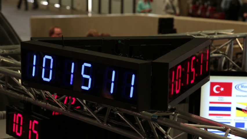 Electronic clock shows time spin at business convention fast motion. Business men and woman walk the floors and interact trade show in Las Vegas Convention Center. Annual meeting and trade show.