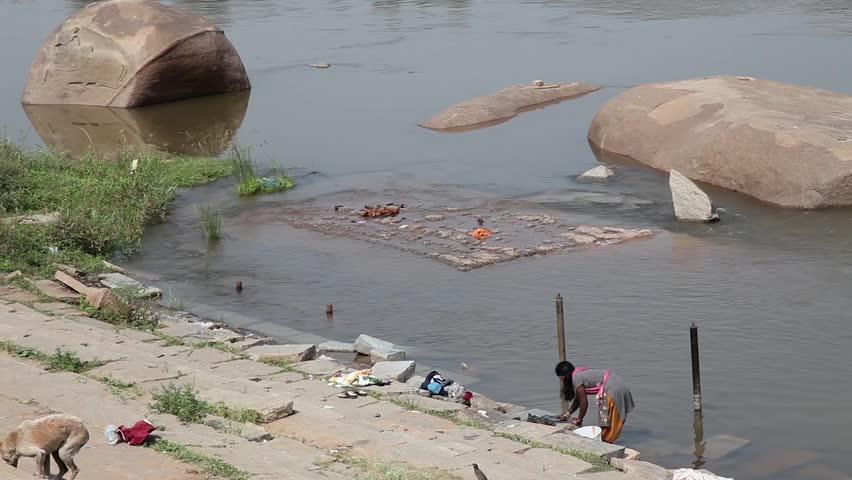 India, Hampi - 30 December 2012: Woman hand washes clothes by the river.