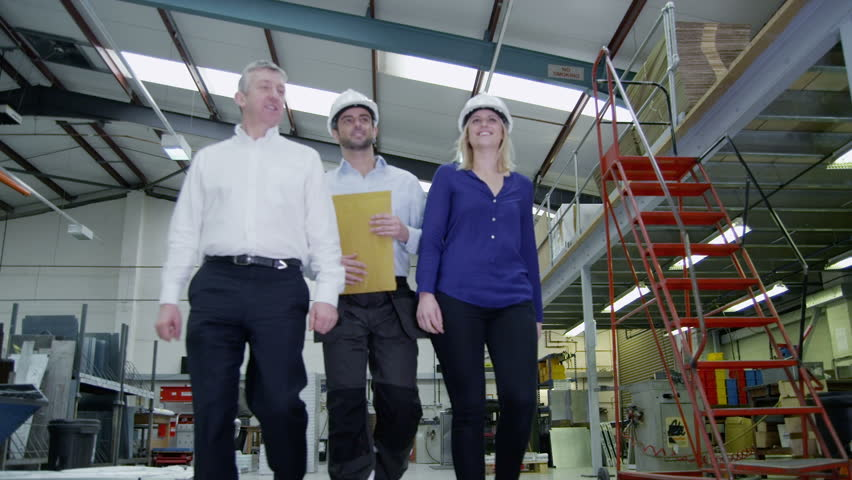 Happy And Friendly Team Of Workers In A Warehouse Or Factory Come Together As They Walk