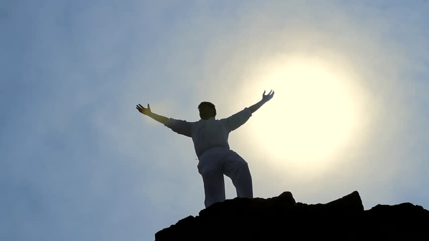 Victory Pose by Man on Top of Hill Lifting Hands at the Sun Business Background