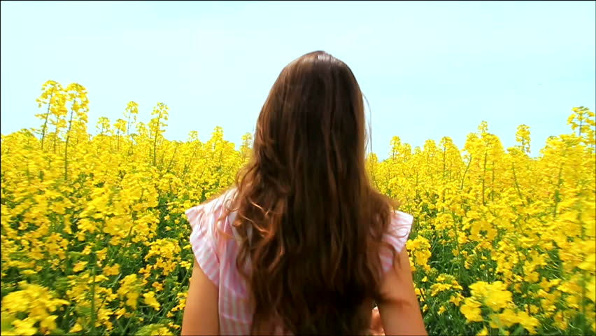 Young Woman in Vintage Dress Running through Yellow Field Touching Flowers HD