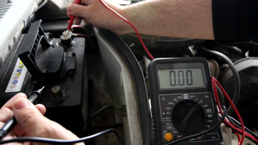Mechanic uses a digital multimeter to check the voltage
