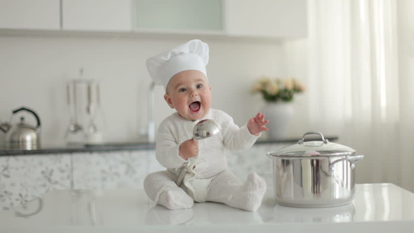 Happy little chef with a ladle knocking on a pan and laughing