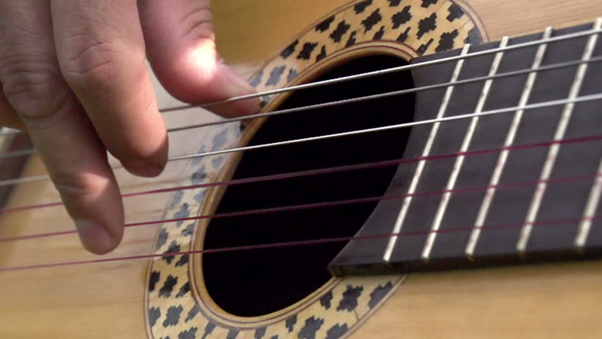 Guitarist. Fingers guitarist slowly pull the strings close up. Slow Motion at a rate of 240 fps
