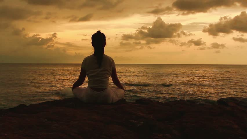 Silhouette of a beautiful Yoga woman in the morning on a beach rock by the sea