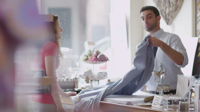 An attractive male store assistant or business owner chats to his female customer as he serves her. In slow motion. | Shutterstock HD Video #3976261
