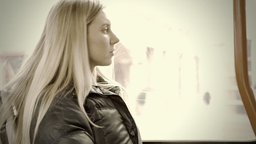 The young beautiful woman sitting in tram
