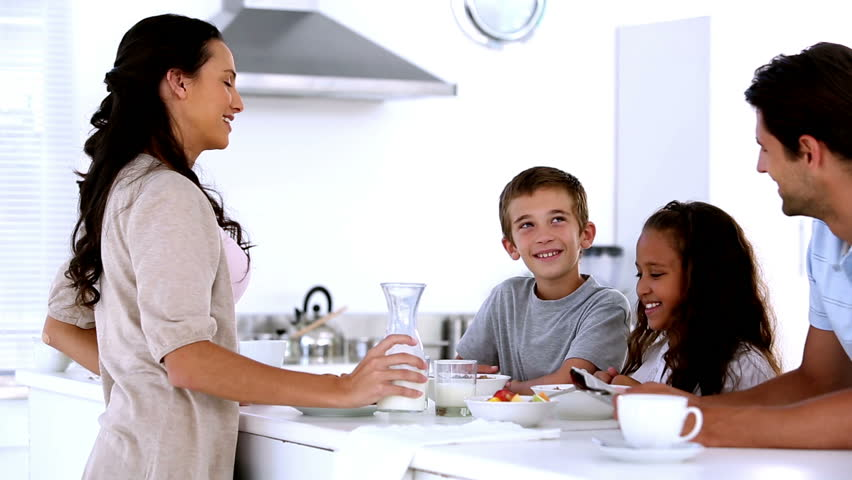 Mother chatting to children at family breakfast and pouring milk in the kitchen at home | Shutterstock HD Video #3989230