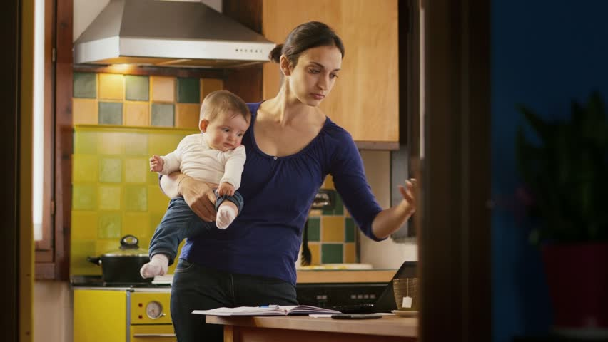 Busy woman talking on the phone in kitchen, multi-tasking mom cooking and working, holding child at home | Shutterstock HD Video #3989842