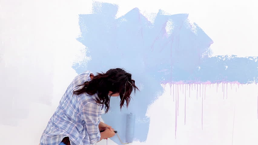 Attractive woman painting her wall in blue
