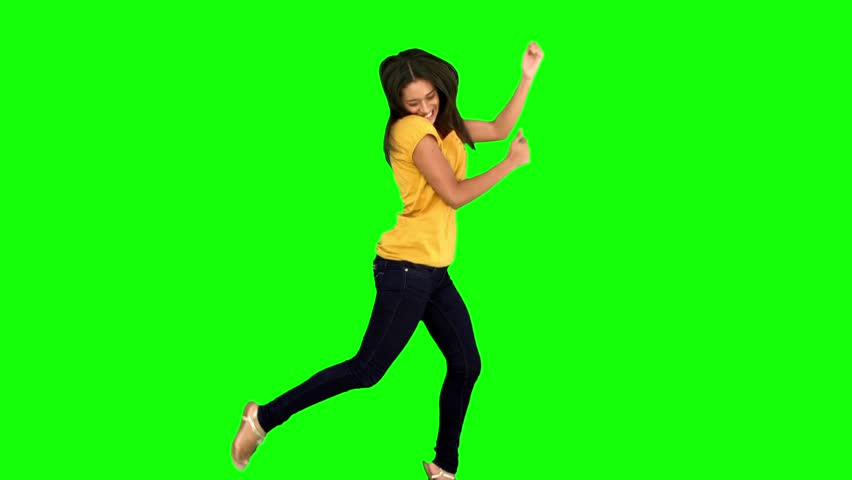 Cheerful woman jumping with legs and arms raised on green screen in slow motion