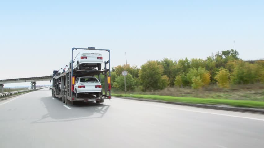 Carrier transports several cars by freeway at summer day, (view from car in motion)