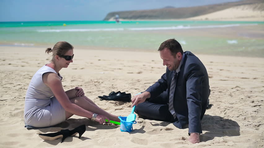 Businesscouple playing on the beach and talking