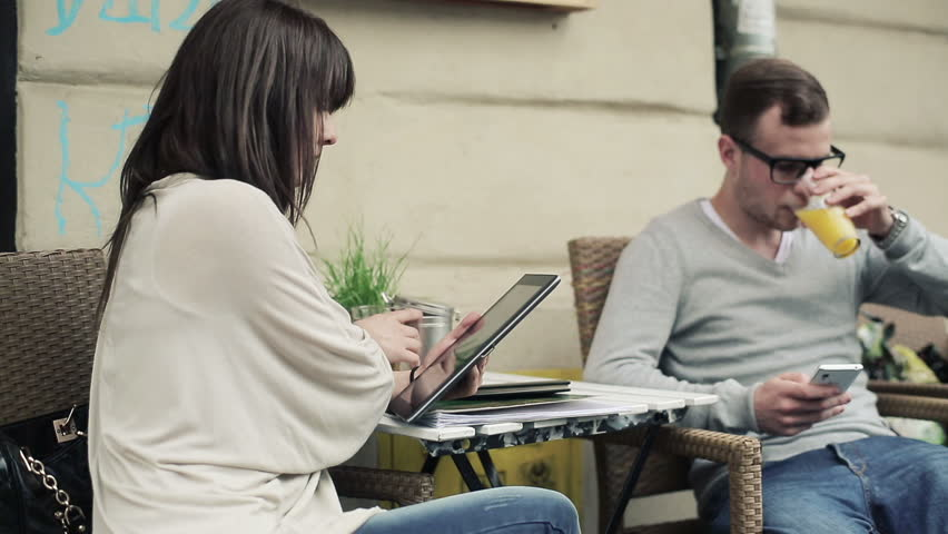 Young students with tablet and smartphone in cafe, steadicam shot