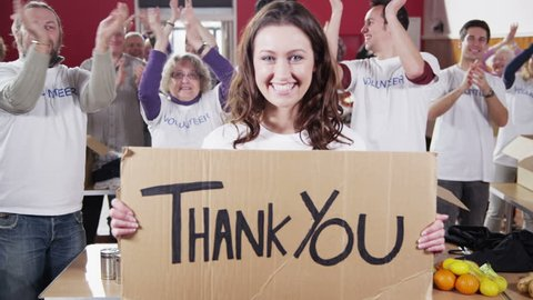 "An attractive female charity volunteer holds up a ""Thank You"" sign and smiles at the camera as her fellow volunteers applaud and cheer in the background."