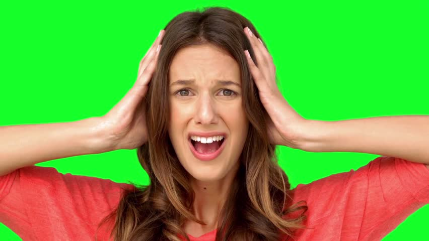 Frustrated woman holding her head between hands on green screen in slow motion