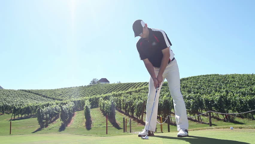 Crane shot of a man golfer that hits a white golf ball with a golf club and the beautiful landscape in the background