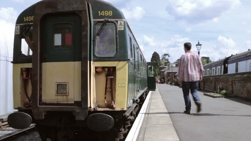 British Railway: A track and pan shot across the front of an old-style British Rail diesel train with a passenger walking towards the train to board in a typical rural British train station.
