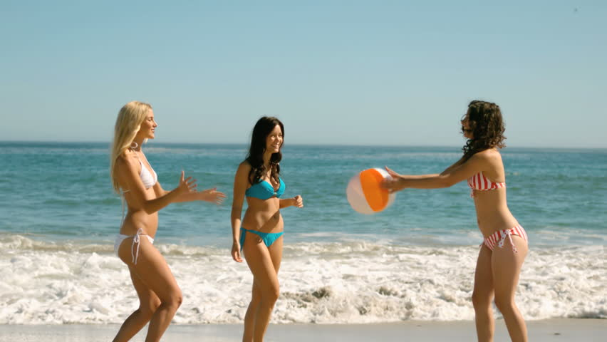 Women playing with a beach ball in slow motion