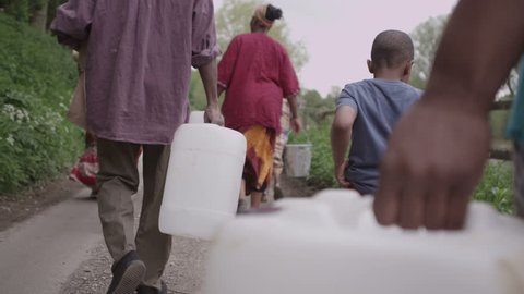 A family group of African villagers travel together with many containers, to find water to bring back to their village. In slow motion.