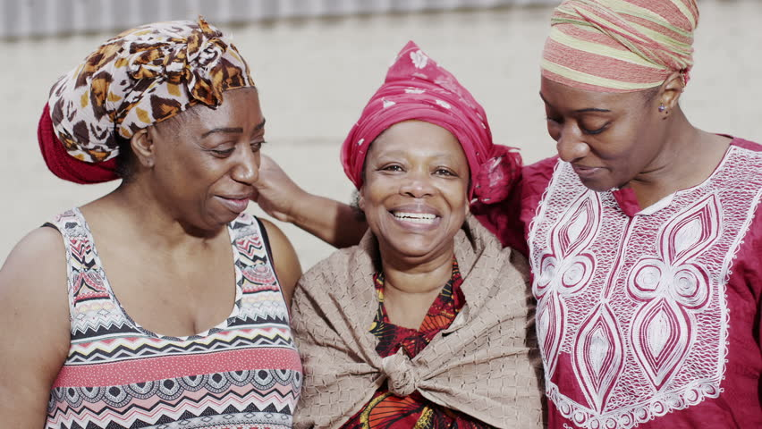 Portrait of three happy smiling African women in traditional dress. In slow motion.