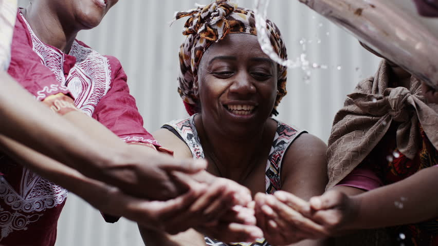 Happy villagers from a poor African community hold out their hands to receive a flowing stream of clear, fresh water. In slow motion. | Shutterstock HD Video #4150666