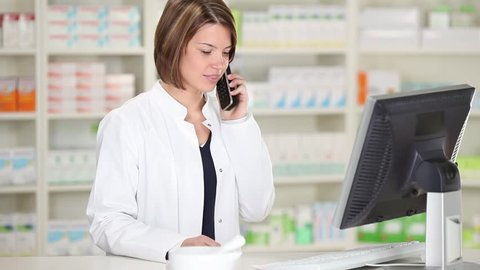 Mid adult female pharmacist using cordless phone while looking at computer in pharmacy