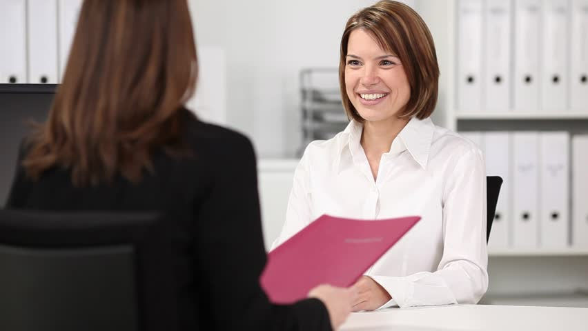 Happy young businesswoman shaking hands with candidate during an interview at desk