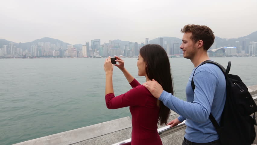 Tourist couple taking photo pictures enjoying view and sightseeing on Tsim Sha Tsui Promenade and Avenue of Stars in Victoria harbour, Kowloon, Hong Kong. Tourism travel concept.