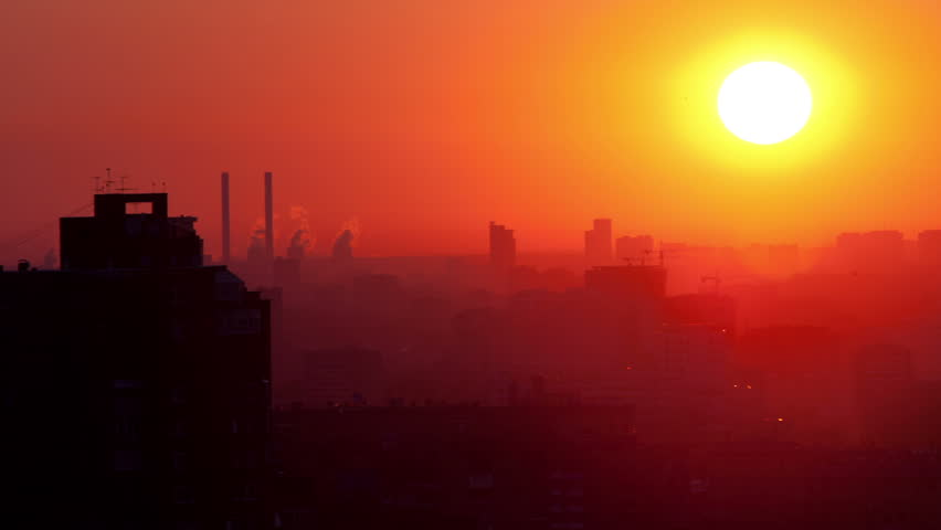 Sunrise over the city. Time lapse. with panning High angle. Aerial view. The roofs of the houses lit by soft warm light