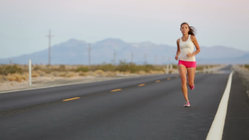 Woman runner running on open road in countryside. Female jogger training for marathon as part of active healthy lifestyle. Mixed race Asian Caucasian girl jogging.