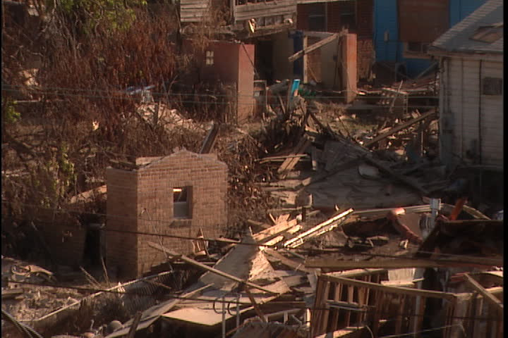 Zoom out from completely destroyed building with car buried in rubble, damaged church in background in New Orleans after Hurricane Katrina (October 2005).