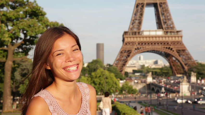 Travel Paris woman waving hello with hand by Eiffel Tower. Happy tourist woman traveling in France, Europe. Travel concept with beautiful young multiracial Asian Caucasian female model.