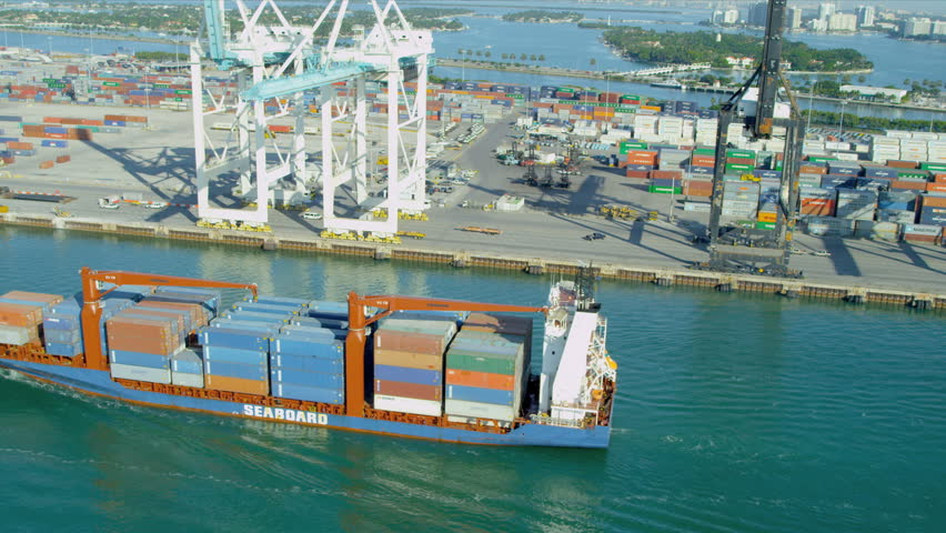 Aerial view PortMiami loaded container cargo vessel leaving port, Biscayne Bay, Miami, Florida, USA