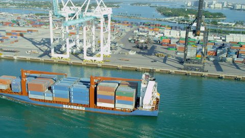 Aerial view PortMiami loaded container cargo vessel leaving port, Biscayne Bay, Miami, Florida, USA