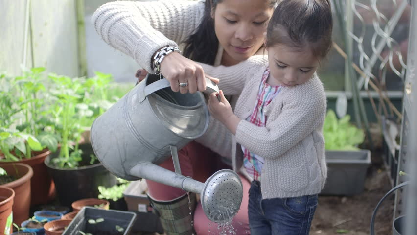 Mother teaching daughter to plant in greenhouse